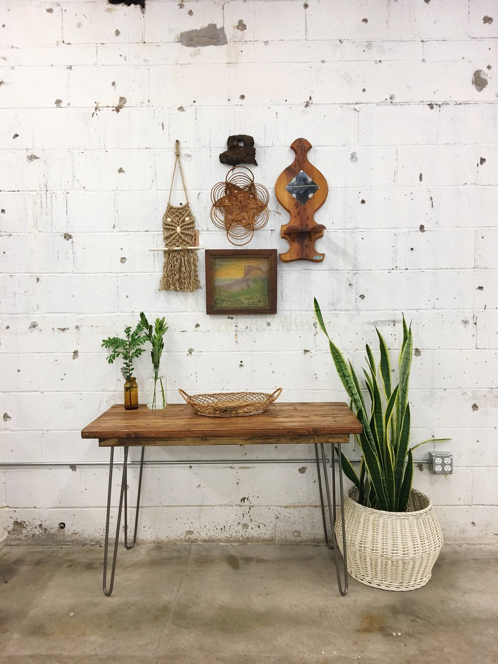 We've hung a variety of objects on the wall including a macrame owl by  House Sparrow Fine Nesting , a piece of driftwood, a basket, a vintage oil painting and a wooden display rack/mirror. This gallery wall may be unconventional, but I sure as hell can't stop looking at it.