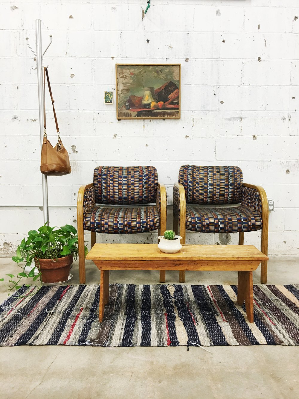 When Ashley Daly posted this scene to Instagram, she described it as feeling like it went together like a warm stew. I think she's correct. The colors from the striped rag rug, the 80s patterned chairs, and the vintage oil painting meld warmly together.