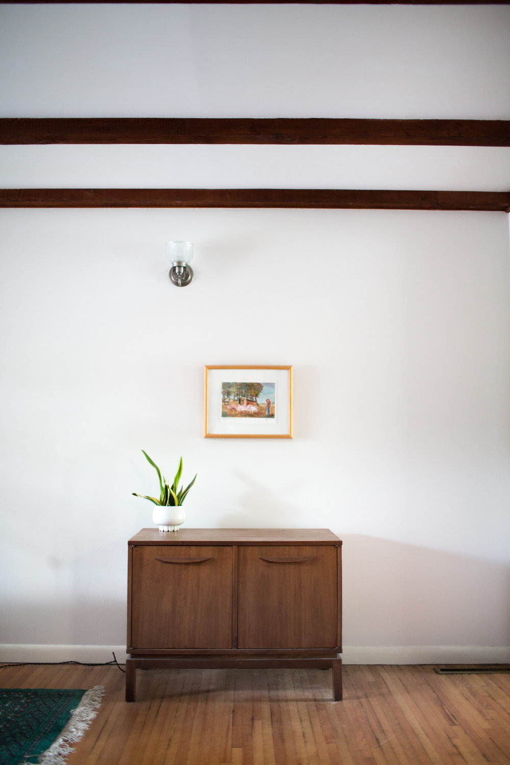 This console (which stands opposite the large built-in) brings a sense of balance to the room by bringing the dark wood to this side of the room. Also, notice the light wood frame hung right above and the dark wood beam at the top. Wood, wood and more wood! Photo Credit: KET Photography