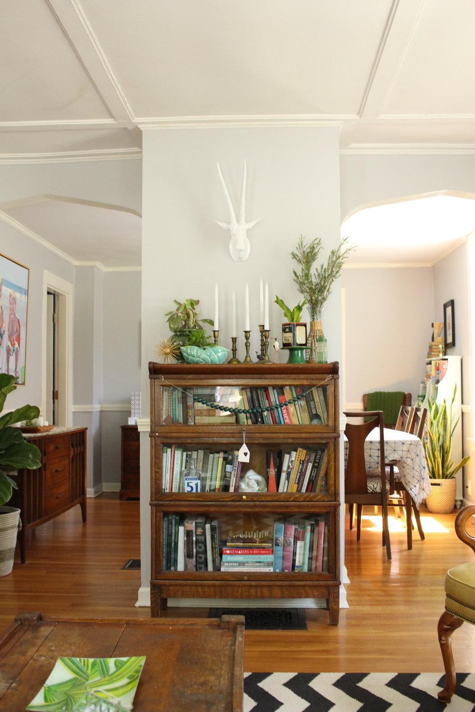 Zandra Zuraw's living room. Bookcase! Plants! Brass!