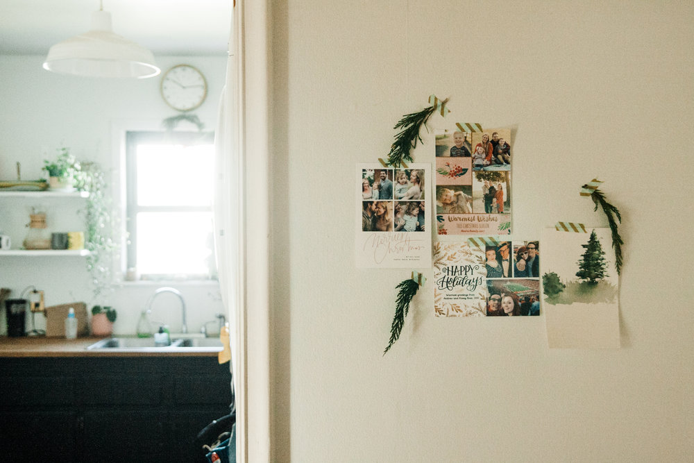 What the hell do you do with all those holiday cards? I started taping them to an empty wall in the growing shape of a Christmas tree. This year I added greenery clippings. What do you think?