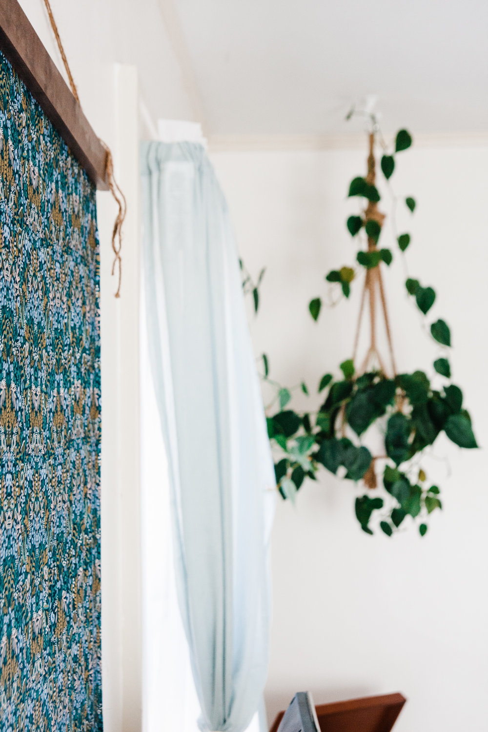 Rifle Paper Co fabric from  Owl & Drum  hangs on the living room wall from a simple wooden frame Emily DIYed.