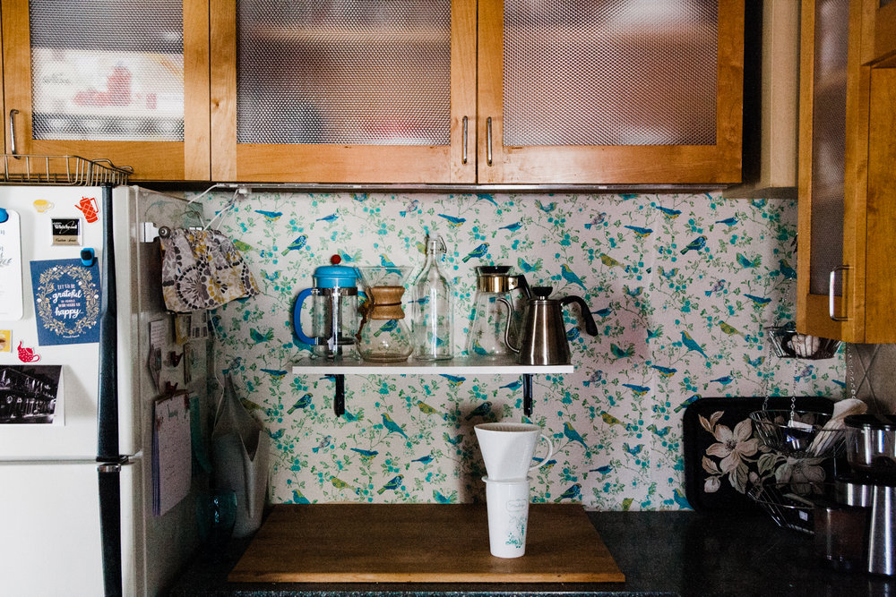 The colorful bird backsplash is fabric that Emily installed herself.