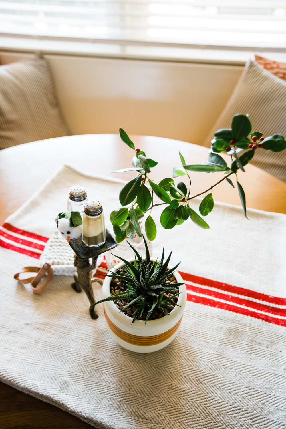 My trusty red striped grain sack (from the first year we owned Retro Den) graced the    eat-in table    this year. And a branch from our weird holly tree-bush plus a succulent and a snowman head makes for a festive eating experience.