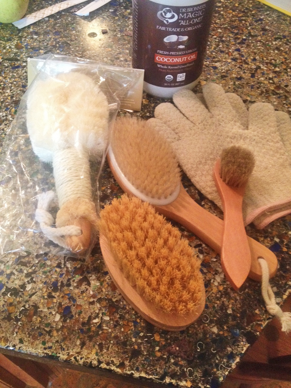 Essentials for nourishing your body's largest organ – THE SKIN: a loofah brush, dry brushes, exfoliating gloves, and organic, raw coconut oil.