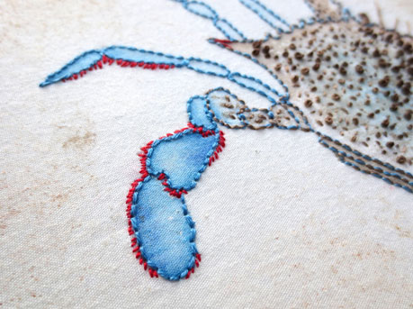 Detail of the blue crab watercolor and stitching.
