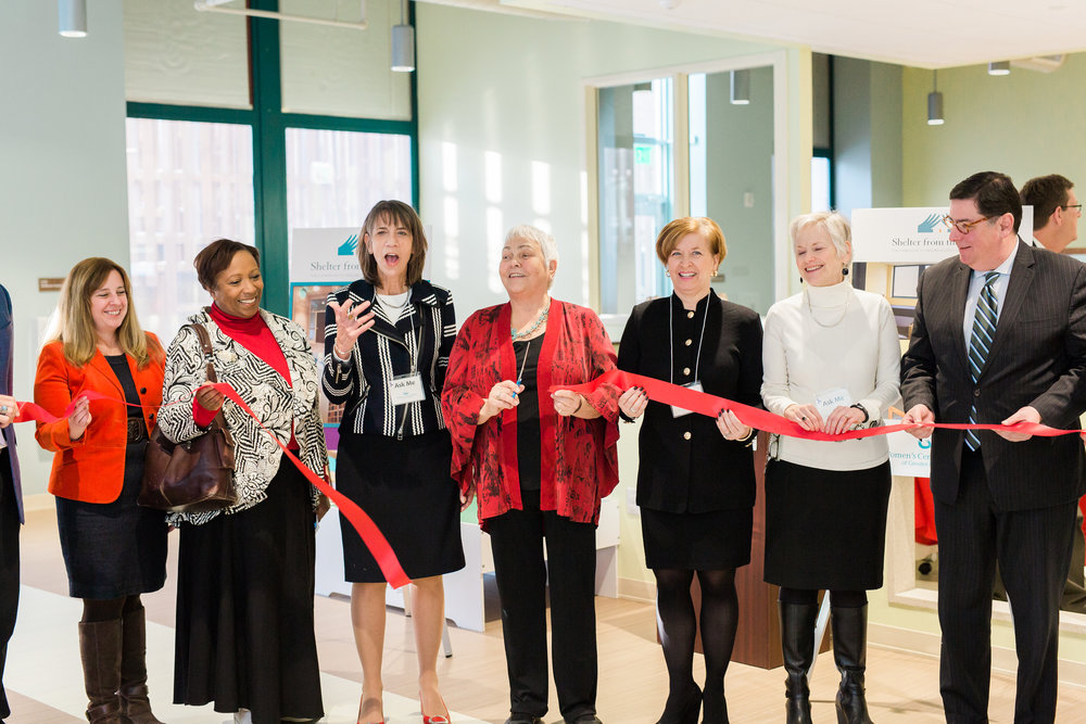 Photo courtesy of Loren DeMarco     Shirl Regan and supporters cut the ribbon on the renovated Women's Center & Shelter, December 2017