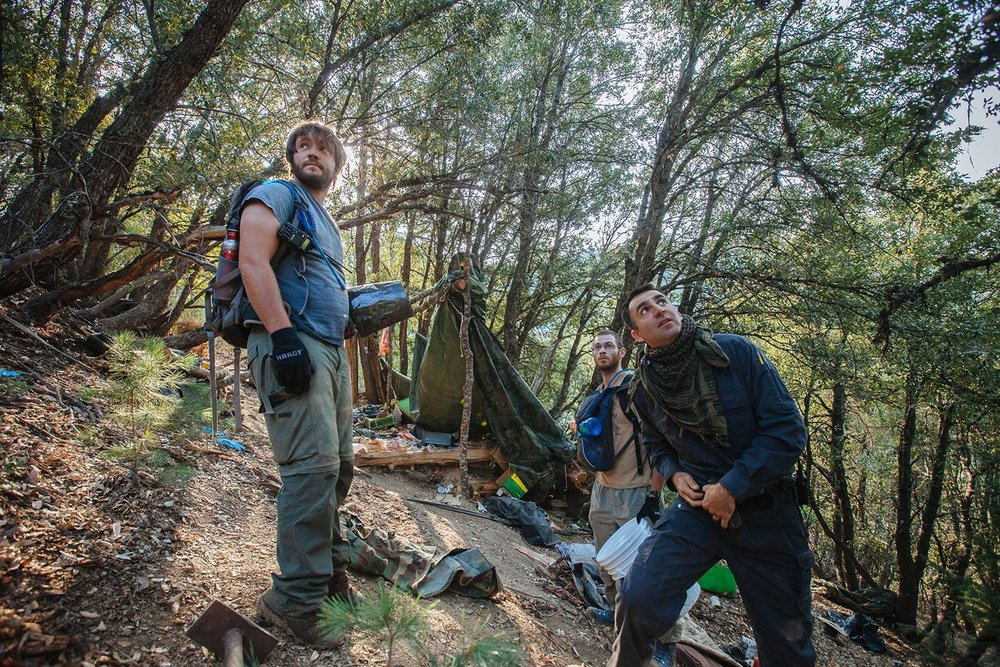 Mourad Gabriel, front right, executive director of the Integral Ecology Research Center, and two of his assistants begin to assess the scope of damage at one of the camps within a grow site in the Plumas National Forest. A member of the team had just found a suspicious package hanging from a tree. The package turned out to be a poison trap full of carbofuran, a highly lethal neurotoxin. Growers will booby-trap their campsites to keep wildlife from coming into living quarters, which are strewn with garbage and food.  PHOTOGRAPH BY MORGAN HEIM