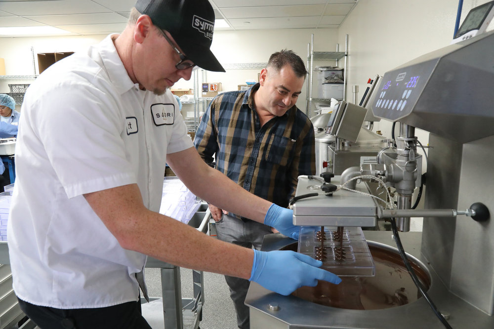 Dennis Hunter, right, a co-founder of CannaCraft, a marijuana business in Santa Rosa in Sonoma County, watching Matt Kulczycki filling a mold with cannabis-infused dark chocolate. Credit Jim Wilson/The New York Times