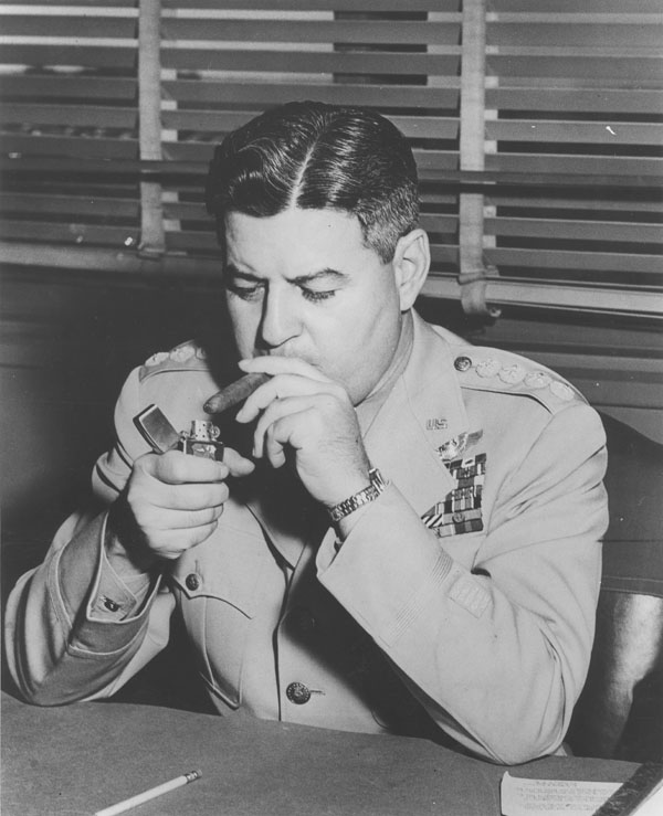 Curtis LeMay at the height of his power in 1957, lighting his ubiquitous cigar with all the money he scored the Air Force. (Image: NSA Archive, GWU University - Public Domain).