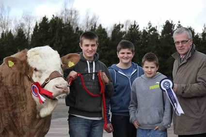 John Henning, head of agricultural relations, Danske Bank, congratulates brothers Kyle, James and Sam Hayes, Upper Ballinderry, on winning the male and supreme overall championship with Haystar Cracker