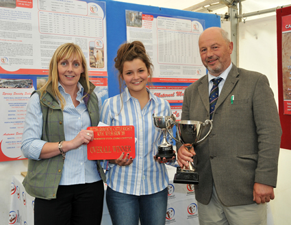 Hannah Wood receives the New Trend Trophy and the Bert Borlase Trophy for Overall Winner, presented by Sponsor Stephanie Denny from the Farmers Guardian and Judge Mr Anthony Davies from the Welston Herd.