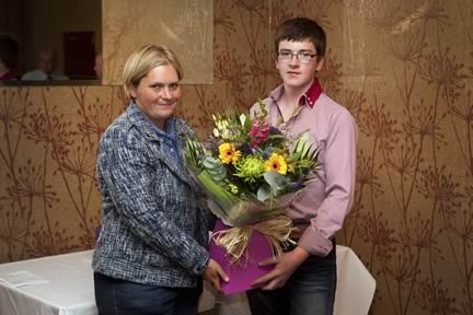 Jamie Boyd receives a bouquet of flowers on behalf of his mother Darla, in recognitiion of all her hard work within the NI club, from YMA co-ordinator Bridget Borlase.