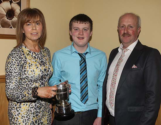 Under 21 stockjudging winner Craig Cowan, Fivemiletown, receives the Carnkern Cup from club chairman Nigel Glasgow, and his wife Phyllis.