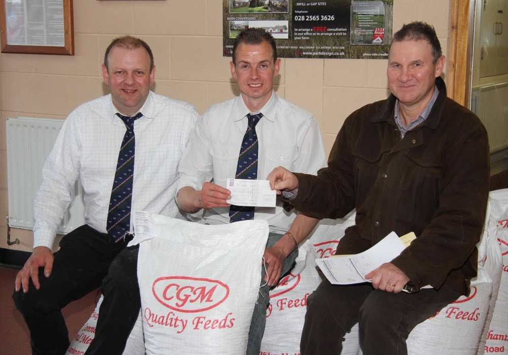 Mike Frazer, right, Edenvale Simmental Herd, Kells, purchased the top price bull at 4,800gns and received the buyers bonus cheque for £200, from club chairman Richard Rodgers. Looking on is Matthew Cunning, Connons General Merchants. Picture: Julie Hazelton