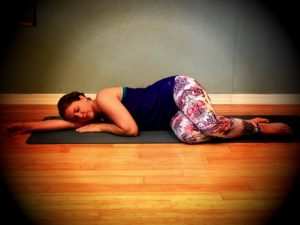 Fetal Position - Lie on your side on the mat, resting your head on your arm, and allowing your knees to bend and rest on the ground.