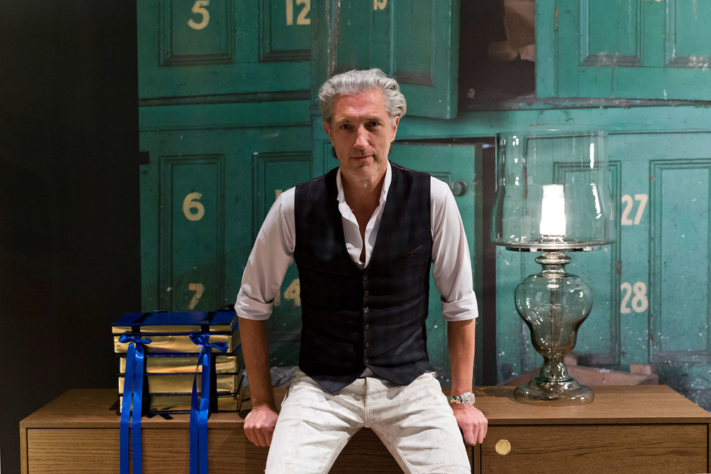 Designer Marcel Wanders perched on the Zio buffet at the 2016 Milan Design Week. Photo: Filippo Bamberghi / Space Furniture