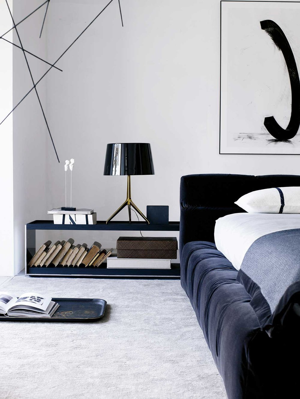 A   Foscarini Lumiere table lamp   sits on a large side table beside a   B&B Italia Tufty-Bed  .