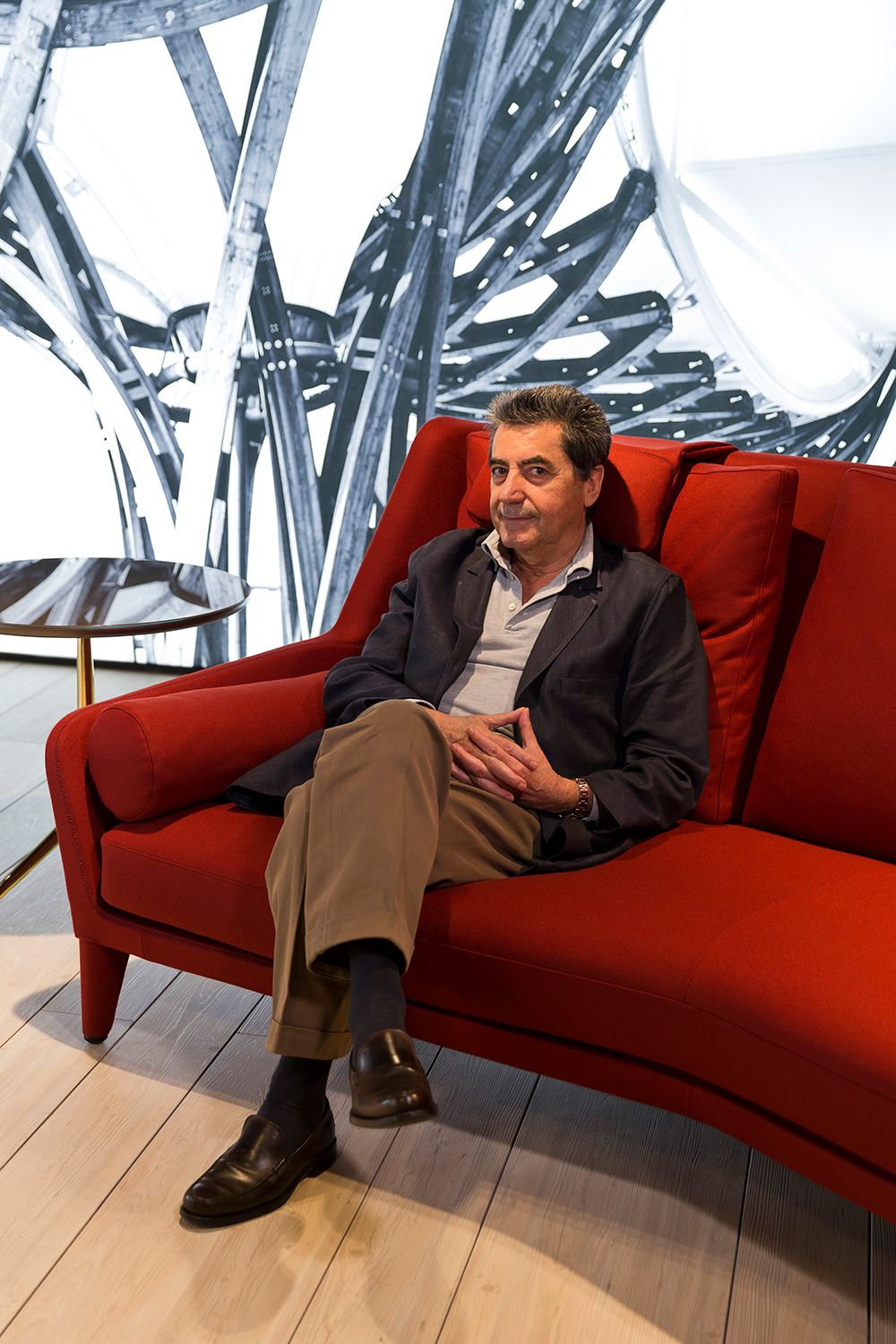 Designer Antonio Citterio sitting on his Édouard sofa, designed for B&B Italia, at the 2016 Milan Design Week. Photo:  Filippo Bamberghi / Space Furniture