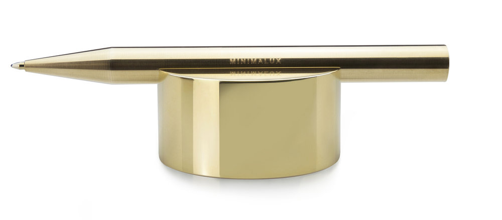 This desk accessory functions as a paperweight whilst providing an ordered resting place for a single pen or pencil.