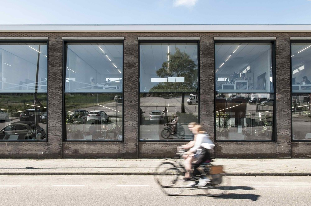 Located in Amsterdam Noord, the former machinery factory has been transformed into offices for Joolz. Reversing the typical office development, the interior is opened up, circulation happens along the edges and glazing is angled to further improve transparency to the street.