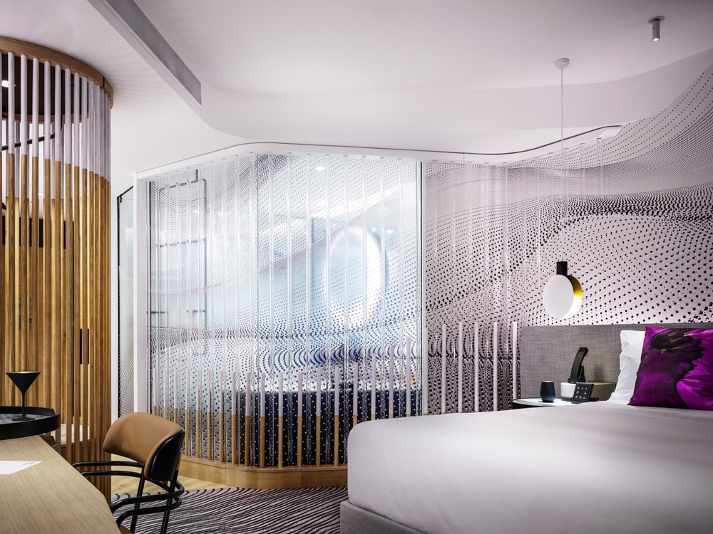 The W Hotel Brisbane layers materials and colour, creating interesting and unexpected spaces within each hotel suite, including the circular timber wardrobes and open plan bathing areas. Photography Justin Alexander.