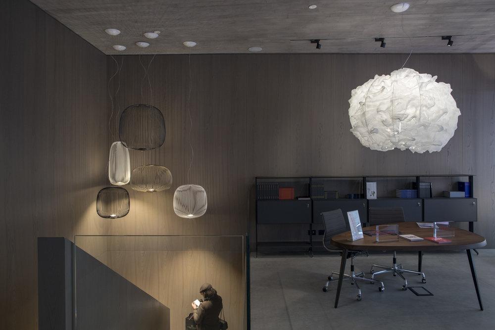 The Nuée lamp (right) designed by Marc Sadler inside Foscarini's new concrete-lined Milanese showroom. Photo © Foscarini.