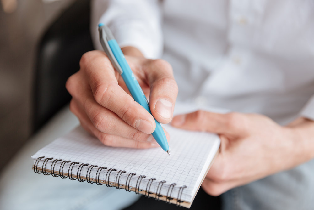 graphicstock-cropped-image-of-young-man-dressed-in-white-shirt-writing-notes-in-notebook-coworking_H_M3ZQoInx.jpg