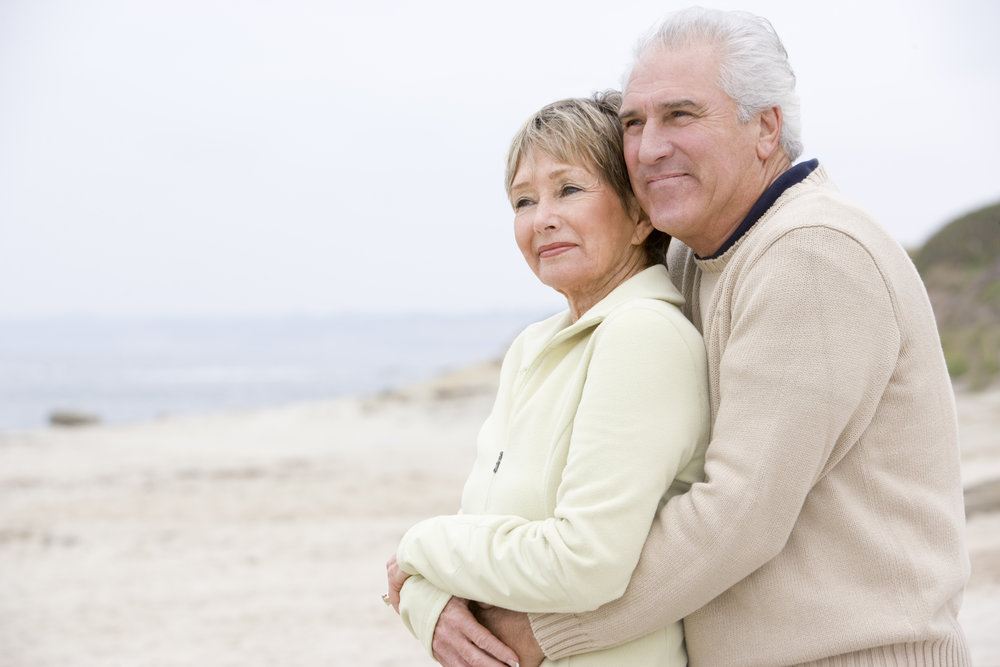 couple-at-the-beach-embracing-and-smiling_SKXgaqCHi.jpg