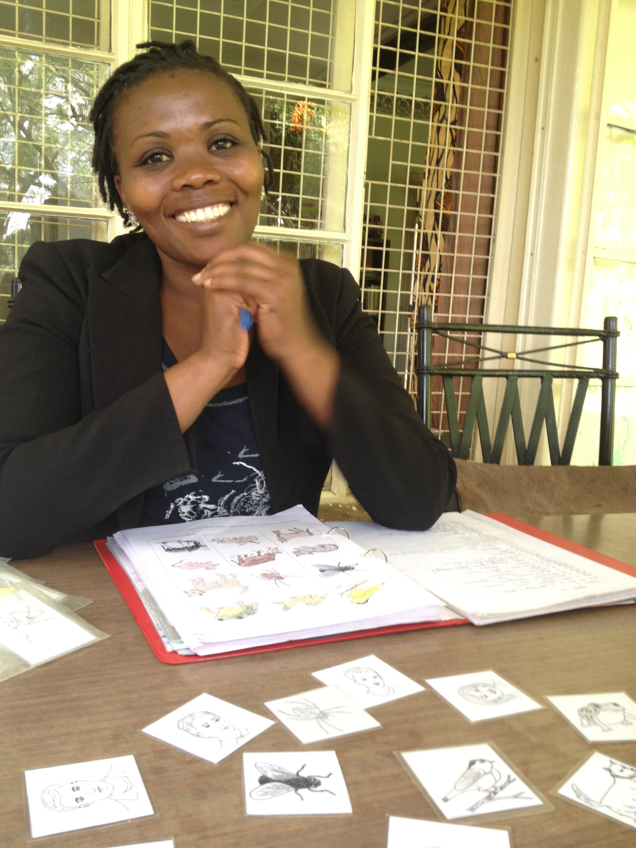 Our wonderful language tutor, Beatrice, smiles after she places some of our Swahili word flash cards on the table.