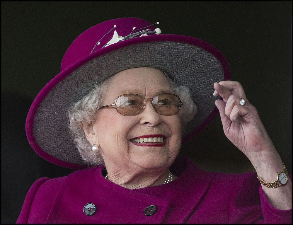 the queen crosses her fingers as she cheers on one of her horses at newbury races