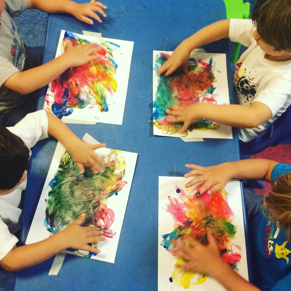Toddler painting in class.