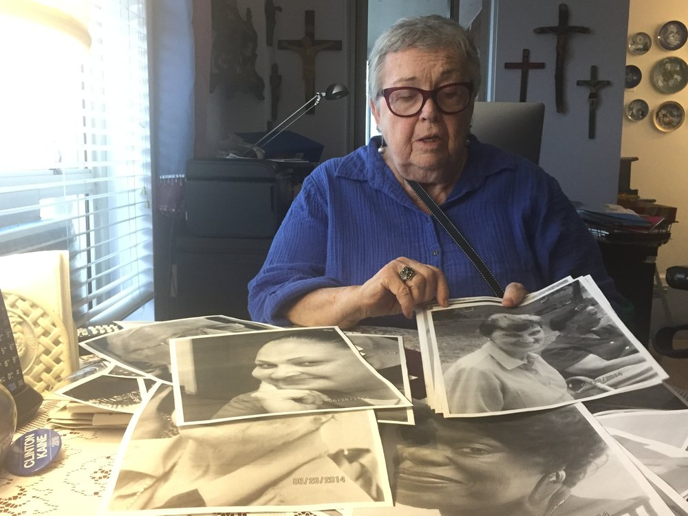 Eileen Canty, 83, shows photos of Morningside Gardens NORC residents at her home. (Photo: Emily Dugdale).