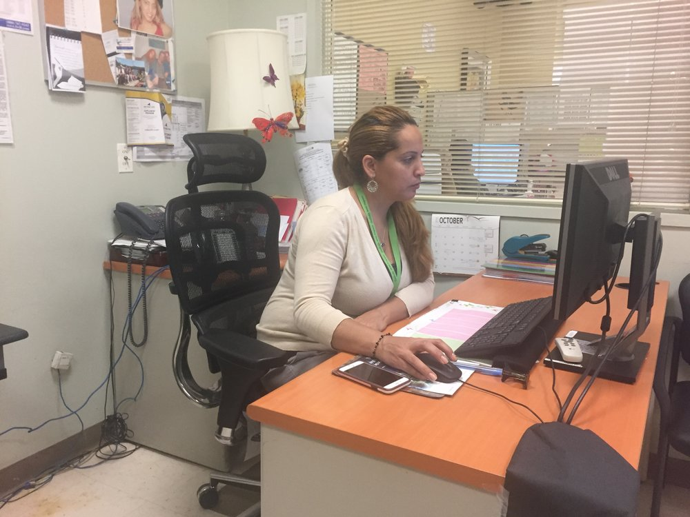 Millie Almonte, a client services manager at Isabella Senior Center, works at her desk. A rainy Friday afternoon brings in few NORC residents looking for senior services (Photo: Emily Dugdale).