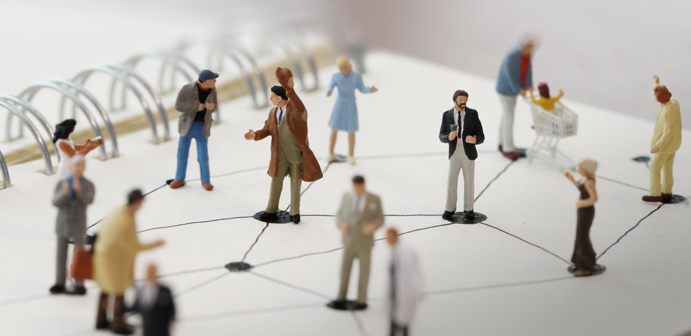 close up of miniature people with social network diagram on open