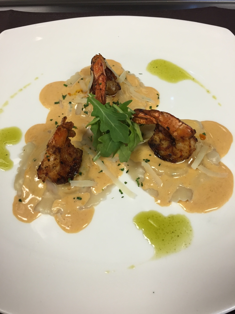 lobster ravioli with cream sauce and blackened shrimp