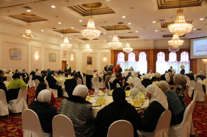 A crowded room of Islamic women listen intently to the Sheikha talk about the importance of good deeds. (Photo by Charlotte Grieve)