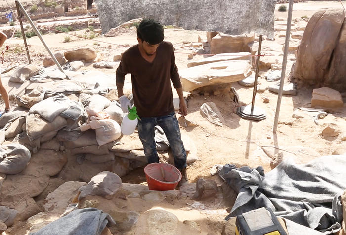 An archaeologist makes mortar to shore up walls.