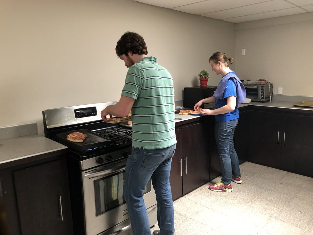 Eric and Rachel warming up pizza for clients of the El Faro program.