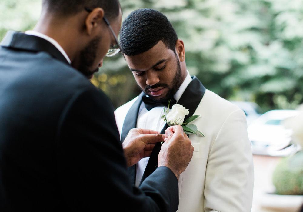 seattle groom gets boutonniere pinned.jpg