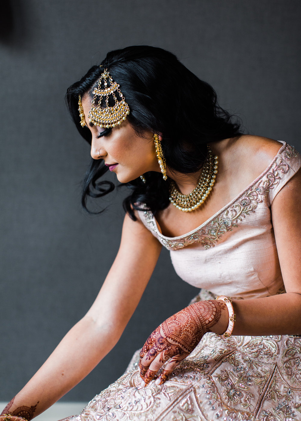 Alexandra Knight Photography Seattle Indian Wedding Photographer bride getting dressed blush pink lehenga dress with gold jewelry and henna.jpg