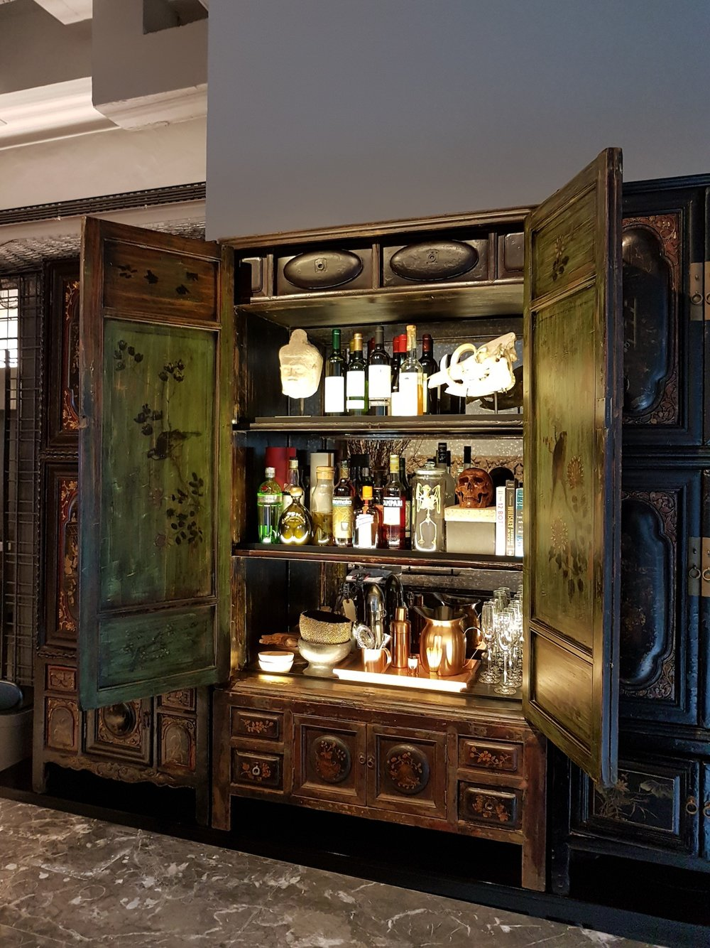 Antique cabinet converted into a bar. Corporate office, styling and photo courtesy of eco-id architects Singapore.