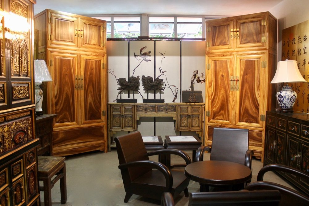 Back (left & right): a pair of Camphor wood compound cabinets. Middle: a pair of wooden antique lions on a long carved Fujian sideboard. Front (right): A French Vietnamese Art Deco armchair set.