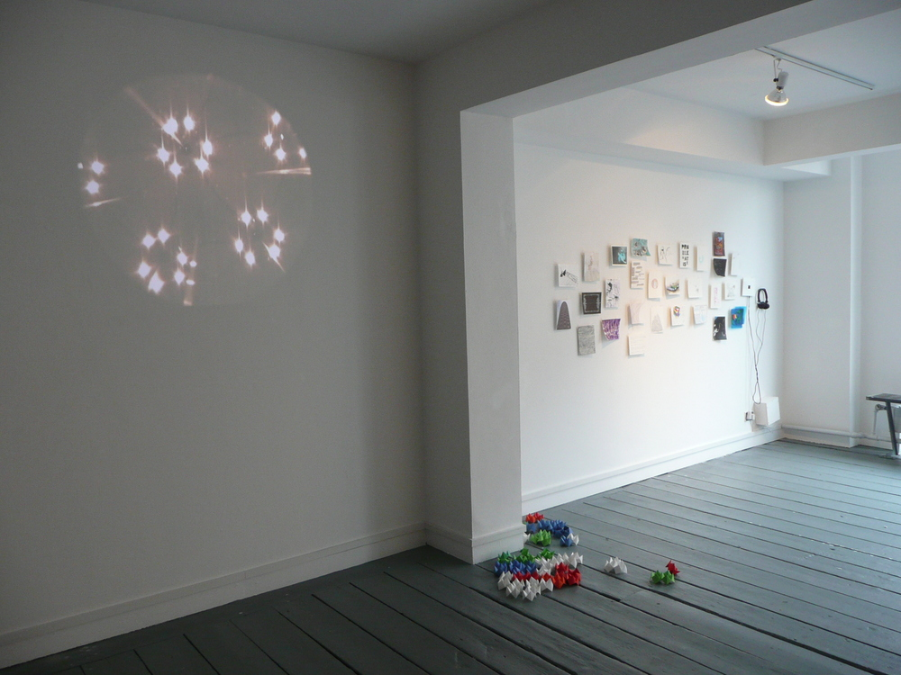 """Left -Paul Murnaghan, A series of attempts to record reality: No. 4(efficacy), 2008, dvd projection.*We met Paul, were given monoscope, shot studio 6, returned monoscope, Middle -Monica Flynn ( work on paper 30.) Elements towards an expandinggeometry of chance and circumstance, origami & audience participation. Right - works on paper by various artists.                      Normal   0           false   false   false     EN-IE   JA   X-NONE                                                                                                                                                                                                                                                                                                                                                                           /* Style Definitions */ table.MsoNormalTable {mso-style-name:""""Table Normal""""; mso-tstyle-rowband-size:0; mso-tstyle-colband-size:0; mso-style-noshow:yes; mso-style-priority:99; mso-style-parent:""""""""; mso-padding-alt:0cm 5.4pt 0cm 5.4pt; mso-para-margin:0cm; mso-para-margin-bottom:.0001pt; mso-pagination:widow-orphan; font-size:10.0pt; font-family:""""Times New Roman"""";}                            Normal   0           false   false   false     EN-IE   JA   X-NONE                                                                                                                                                                                                                                                                                                                                                                           /* Style Definitions */ table.MsoNormalTable {mso-style-name:""""Table Normal""""; mso-tstyle-rowband-size:0; mso-tstyle-colband-size:0; mso-style-noshow:yes; mso-style-priority:99; mso-style-parent:""""""""; mso-padding-alt:0cm 5.4pt 0cm 5.4pt; mso-para-margin:0cm; mso-para-margin-bottom:.0001pt; mso-pagination:widow-orphan; font-size:10.0pt; font-family:""""Times New Roman"""";}"""