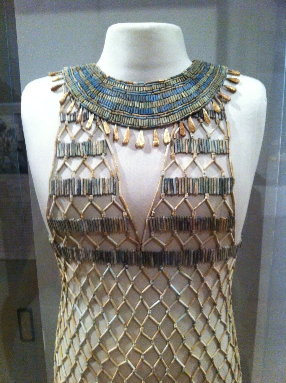 Detail, bead-net dress and broad collar whose remains were found during excavations of the tomb of a female interred at Giza during the reign of King Khufu, ca. 2500 BCE. Both pieces were reconstructed by Millicent Jick (1928-2010), a volunteer gallery instructor at the Museum of Fine Arts, Boston.  The cylinder and disk beads are Egyptian faience. The pendants on the broad collar are made of gold. Image courtesy Museum of Fine Arts, Boston.