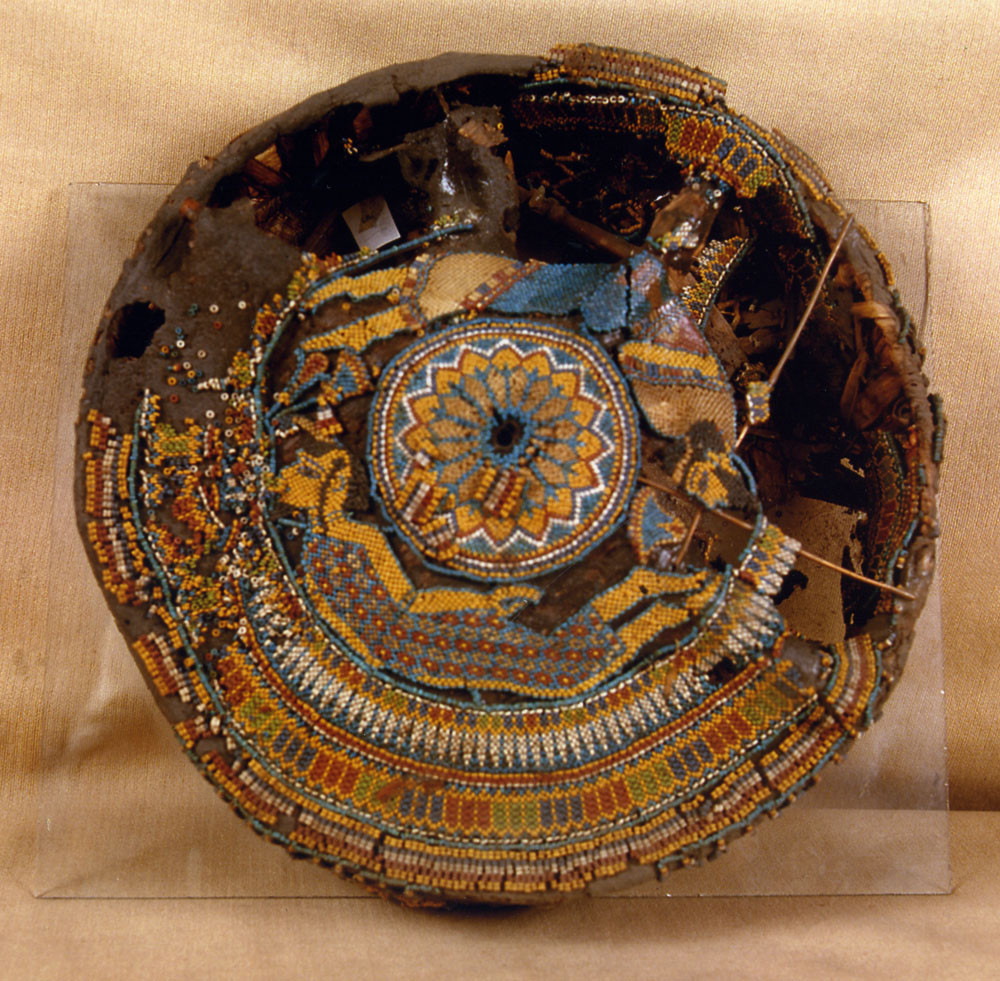 Above - one of the beaded hassocks found in the tomb of King Tutankhamun, yielding the earliest known renderings of the human figure in beads, ca. 1332-1323 BCE.  A common motif in King Tut's day, the figures represent the African and Asiatic enemies of Egypt - one of the earliest surviving examples in beadwork of thematic content, in this case, of a sociopolitical nature.  The technique looks to be one- and two-drop peyote stitch. The hassock is preserved at the Egyptian Museum in Cairo. Image courtesy Egyptian Museum, Cairo.