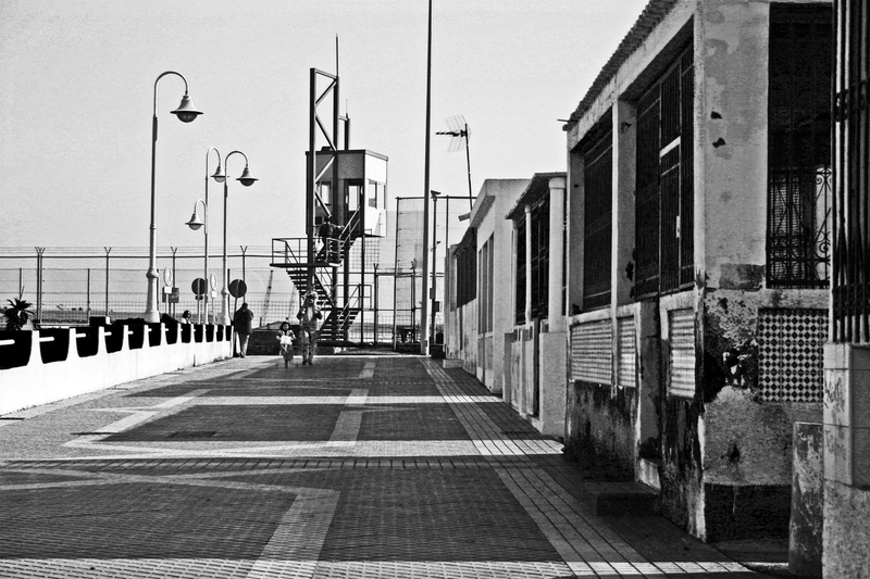 The boardwalk in Melilla, Spain with a border fence guard tower in the background.
