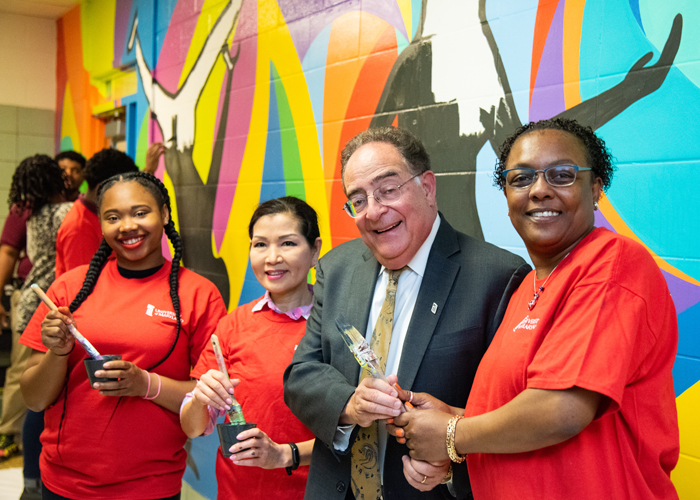 Taking a break from painting, (from left) Dyelle Washington, a sophomore at Renaissance Academy, MD First Lady Yumi Hogan, UMB President Jay A. Perman, MD, and Renaissance Academy Principal Tammatha Woodhouse, pose for a picture in front of the colorful mural.