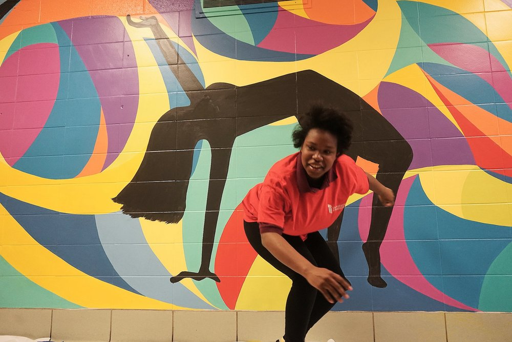 A Renaissance Academy Student poses and dances in front of the colorful mural.