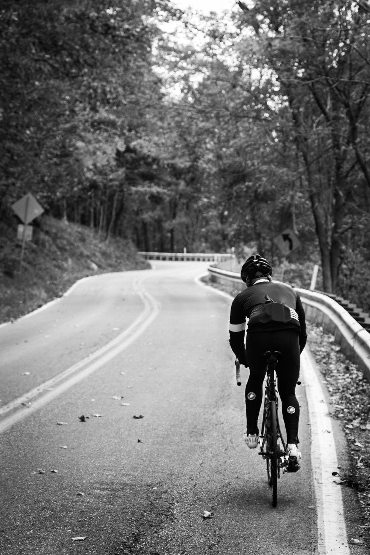 A Bike Rider Climbing Up Road